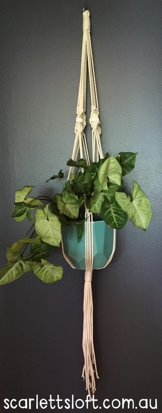 Handmade bohemian macrame hanger with white beads.