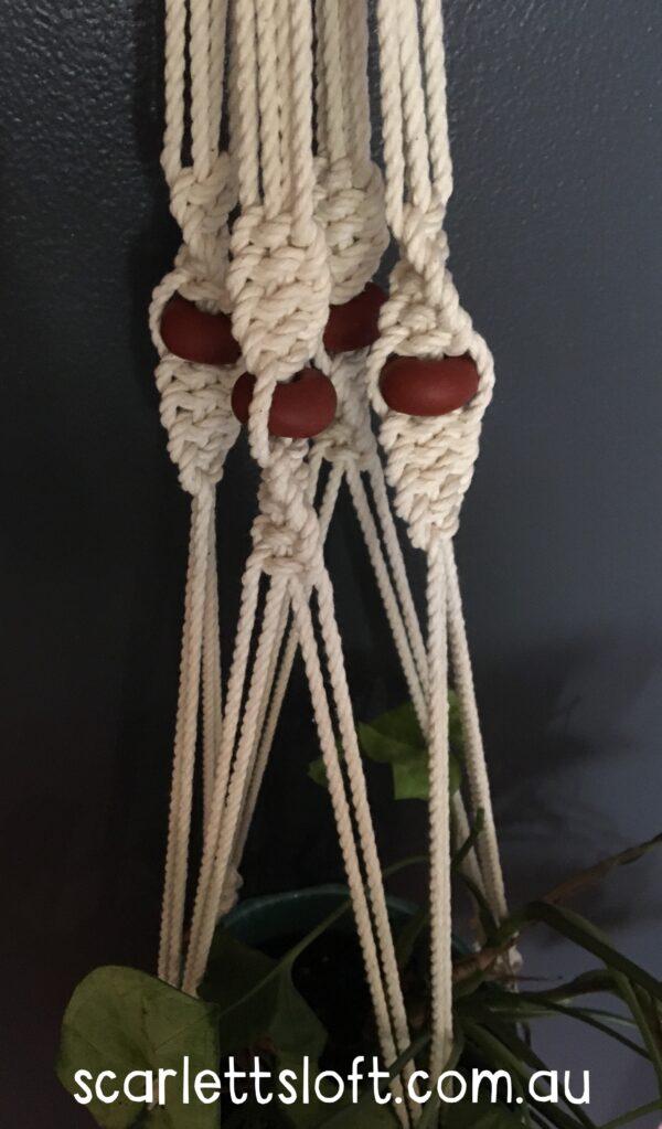 Handmade macrame hanger with brown beads.